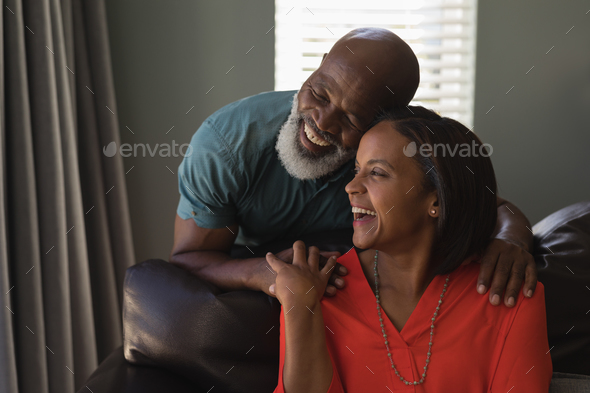 Front view of an active senior couple having fun in living room at home - Stock Photo - Images