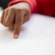 Close-up of blind mixed-race schoolboy hand reading a braille book in classroom at elementary school - PhotoDune Item for Sale