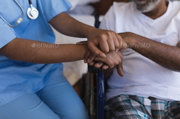 Mid section of young African American female doctor consoling senior African American man at home - Stock Photo - Images
