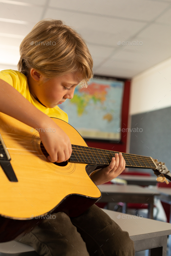 Side view of Caucasian boy playing guitar in a classroom at elementary school - Stock Photo - Images