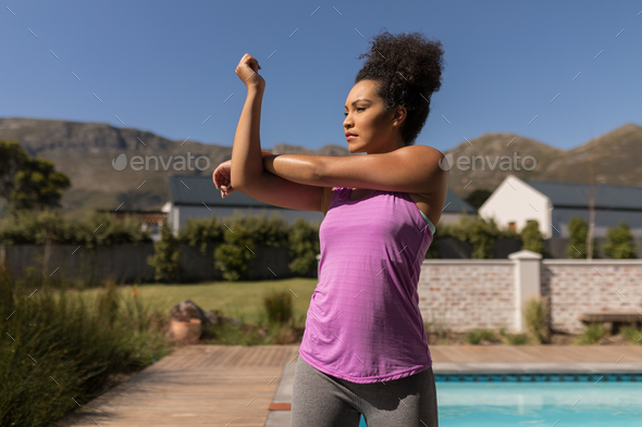 Woman performing stretching exercise next to the swimming pool in the backyard of home - Stock Photo - Images