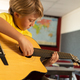 Side view of Caucasian boy playing guitar in a classroom at elementary school - PhotoDune Item for Sale