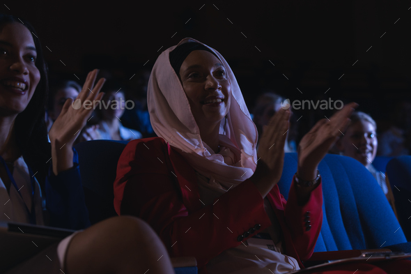 Low angle view of mixed race businesswoman sitting  and clapping in the auditorium - Stock Photo - Images