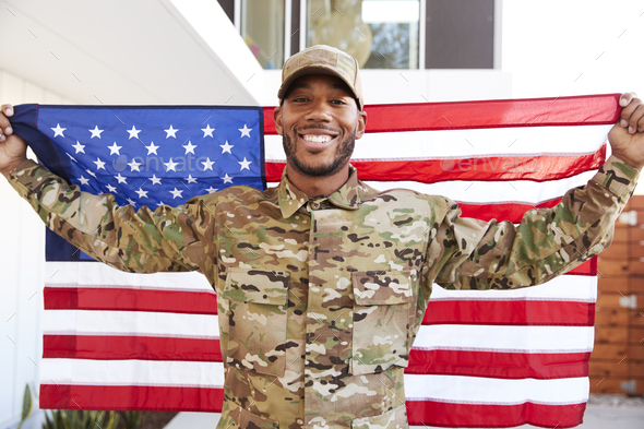 Millennial black soldier standing outside modern building holding US flag, Smiling  - Stock Photo - Images
