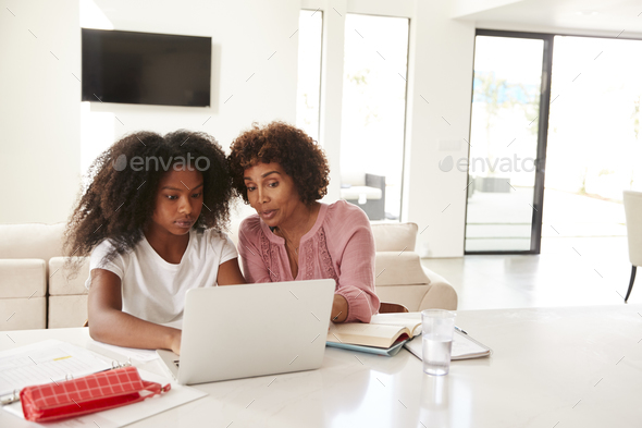 Middle aged black woman helping her teenage daughter with homework, front view - Stock Photo - Images