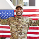 Millennial black soldier standing outside modern building holding US flag, Smiling  - PhotoDune Item for Sale