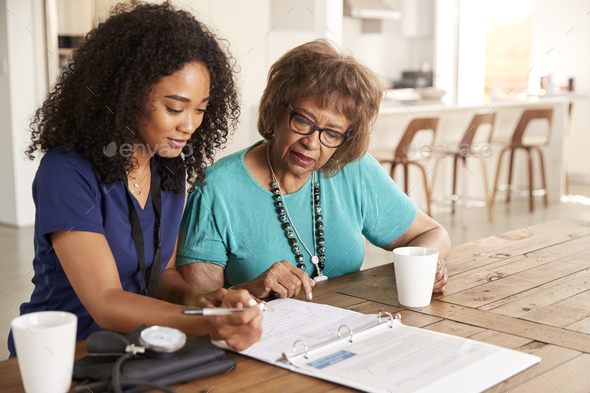 Female healthcare worker filling in a form with a senior woman during a home health visit - Stock Photo - Images