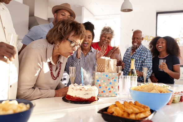 Middle aged black woman cutting cake during a three generation family birthday celebration,close up - Stock Photo - Images