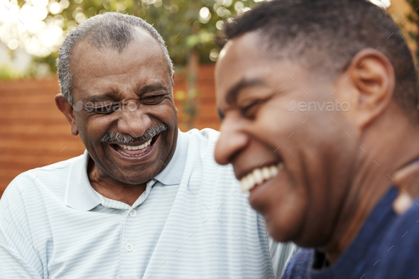 Senior black man and his adult son laughing together outdoors, close up - Stock Photo - Images