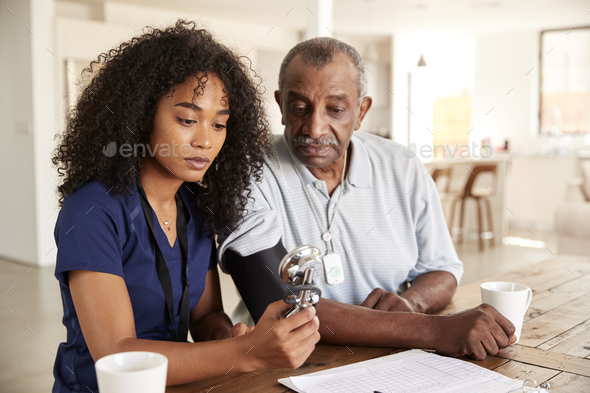 Female healthcare worker checking the blood pressure of a senior man during a home visit - Stock Photo - Images
