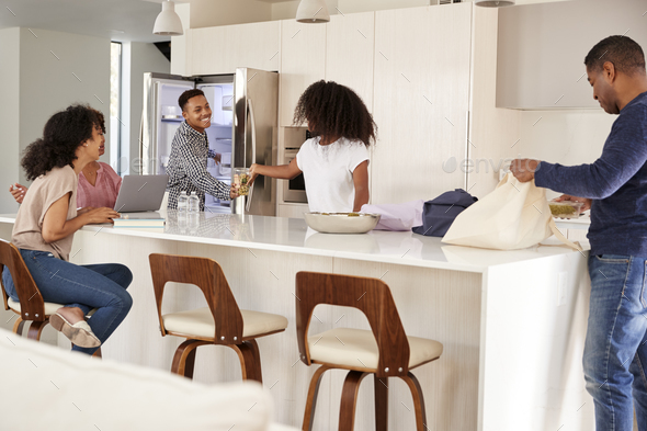 Black family in their kitchen, unpacking groceries and putting them away together - Stock Photo - Images