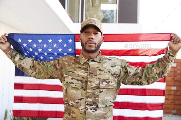 Millennial black soldier standing outside modern building holding US flag - Stock Photo - Images