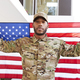 Millennial black soldier standing outside modern building holding US flag - PhotoDune Item for Sale