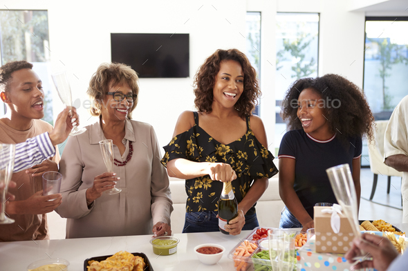 Millennial black woman opening champagne to celebrate with her family,front view - Stock Photo - Images