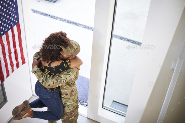 Returning millennial black soldier lifting his wife off her feet in the doorway of their home - Stock Photo - Images