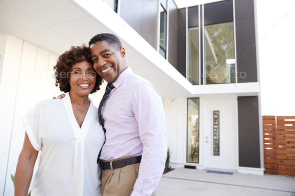 Middle aged black couple stand outside admiring their modern home, back view - Stock Photo - Images