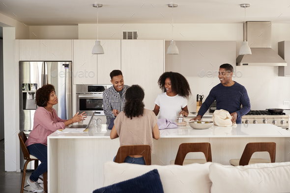 Black family in their kitchen talking and preparing a family meal together - Stock Photo - Images