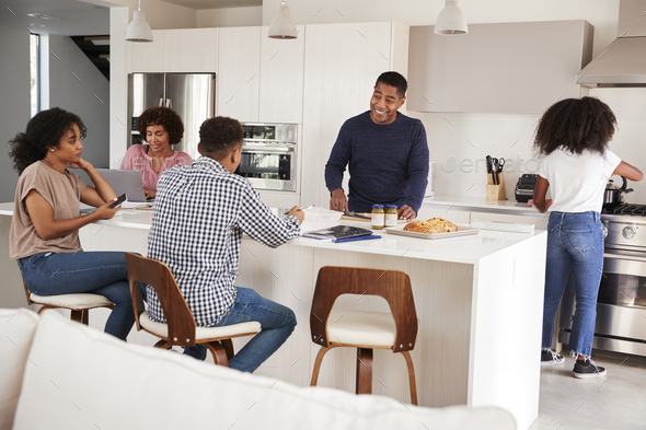 Happy black family talking and preparing a family meal together in their kitchen - Stock Photo - Images
