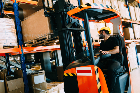 Warehouse worker doing logistics work with forklift loader - Stock Photo - Images