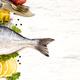 Fresh dorado fish, lemon, olive oil and vintage fork and knife on wooden board - PhotoDune Item for Sale