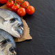 Fresh dorado fish and tomatoes on dark vintage background - PhotoDune Item for Sale