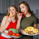 Two sports girl in a kitchen with vegetables - PhotoDune Item for Sale