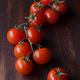 bunch of tomatoes on branch on classic wooden board - PhotoDune Item for Sale