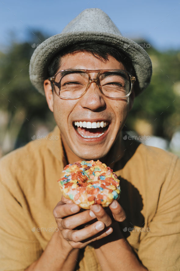 Happy man having a doughnut - Stock Photo - Images