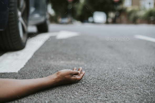 Person lying on the ground after a car accident - Stock Photo - Images