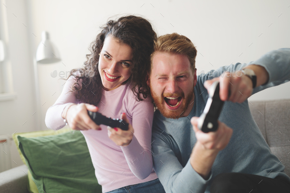 Happy couple playing video games - Stock Photo - Images