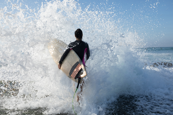 Woman With Surfboard Going To Surf In The Big Waves