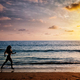 Beautiful athletic woman running along sea beach in the morning - PhotoDune Item for Sale