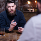 Handsome bearded man looking at his friend and shuffle cards - PhotoDune Item for Sale