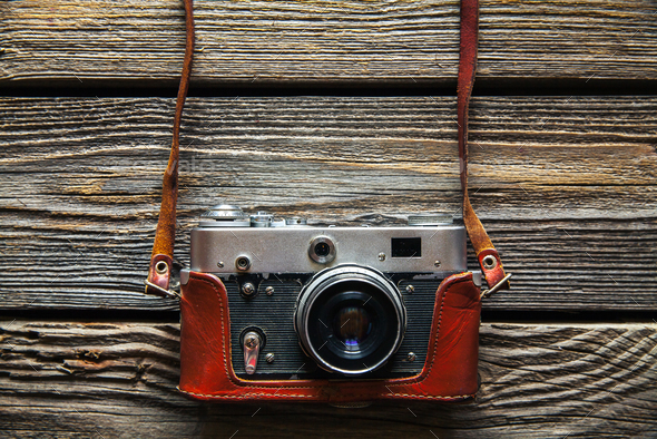 Retro camera on wood table background, vintage color tone - Stock Photo - Images