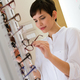 Pretty young woman is choosing new glasses at optics store - PhotoDune Item for Sale