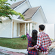 young couple standing in front of their new house - PhotoDune Item for Sale