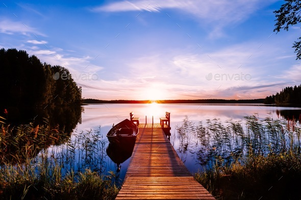 Wooden pier with fishing boat at sunset on a lake in Finland - Stock Photo - Images