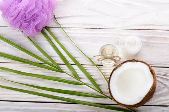 Flat lay Coconut oil in glass bottle bath sponge candle and shel - Stock Photo - Images