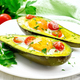 Scrambled eggs with tomatoes in avocado on light wooden board - PhotoDune Item for Sale