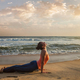 Woman practices yoga asana Urdhva Mukha Svanasana at the beach - PhotoDune Item for Sale