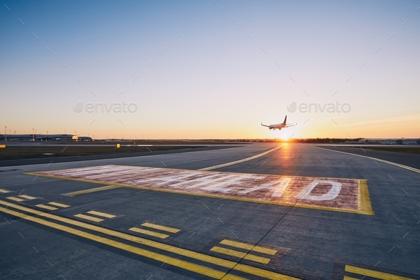 Airplane landing at sunset - Stock Photo - Images