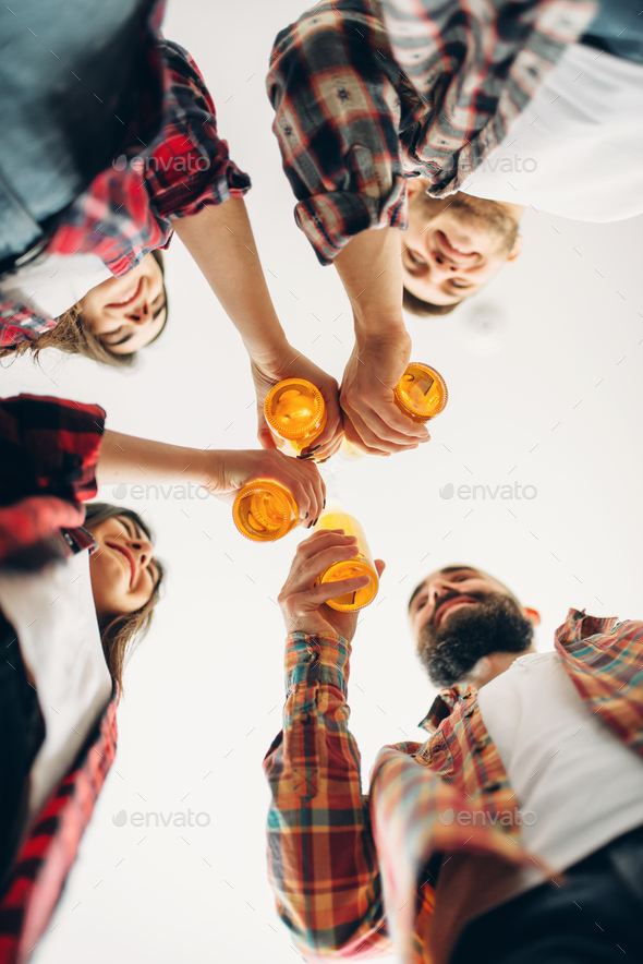 Friends clink bottles with beer, bottom view - Stock Photo - Images