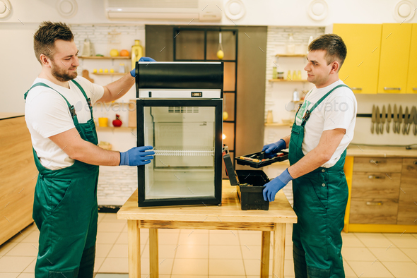 Two workers in uniform repair refrigerator at home - Stock Photo - Images