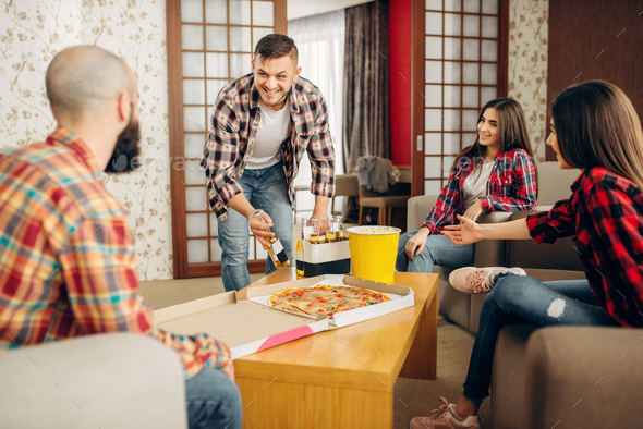 Friends drink a beer with pizza at the home party - Stock Photo - Images