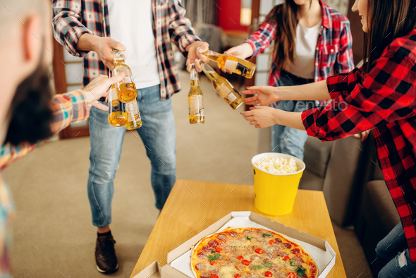 Friends with beer, pizza and popcorn at home party - Stock Photo - Images