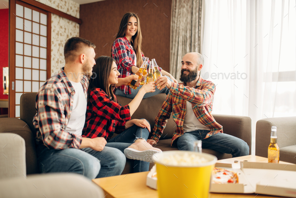 Friends clink bottles with beer at the home party - Stock Photo - Images