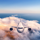 Airplane is flying over the clouds at sunset in summer. Aircraft - PhotoDune Item for Sale