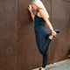 Back view of fit woman stretching after workout against metal wall in the city - PhotoDune Item for Sale