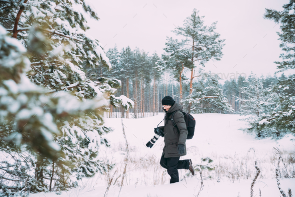 Young Man Backpacker With Photo Camera Taking Photo In Winter Sn - Stock Photo - Images
