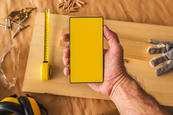 Carpenter holding modern smartphone with blank mock up screen - Stock Photo - Images